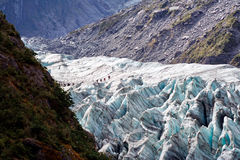 Fox glacier. View of the end of the fox glacier and its numerous crevasses.  A very steep and fast moving glacier.  This allows it to remain frozen while the Stock Photo