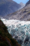 Fox glacier - vertical. View of the end of the fox glacier and its numerous crevasses.  A very steep and fast moving glacier.  This allows it to remain frozen Royalty Free Stock Photography