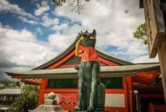 Kitsune Shrine, Fushimi Inari, Kyoto Japan. Fox `kitsune` guardian statue holds golden rice harvest, draped in red cloth in front of temple Stock Image