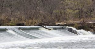 Water Over The Fox River Dam. The Fox River in Illinois is a great place to be outdoors. This dam was blurred on a cloudy day and provided a nice background royalty free stock image