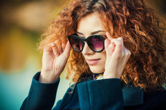 Foxy hair beauty. Autumn style. Beautiful young woman with bright foxy hair wearing sunglasses and black coat. Beauty, fashion Royalty Free Stock Image