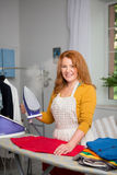 Foxy haired female at home ironing. Smiling mid aged housewife holding iron Stock Images
