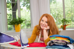 Foxy haired woman finishing ironing clothes. Tired and satisfied housewife standing by ironing board Royalty Free Stock Photography