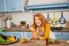 Foxy housewife in the kitchen. Mid aged female cooking helthy food Royalty Free Stock Images