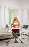 Foxy housewife standing by ironing board. Mid aged woman iat home busy with housekeeping work Royalty Free Stock Photo
