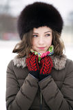 A foxy lady breathing fresh air. Pretty brunette in a black-furred hat looks shy stock images