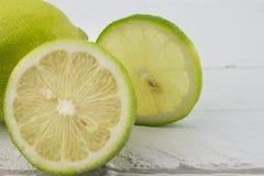 Foyer avant sur le citron demi sur le backgro en bois blanc rustique Photographie stock