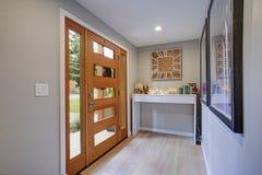 Foyer chic avec une entrée principale en verre de panneau et une table de console blanche photographie stock libre de droits