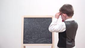 Foyer drôle d'enfant sur le conseil de craie avec le griffonnage de maths, l'étudiant épuisé avec des lunettes et l'uniforme, étu clips vidéos