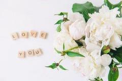 Foyer plat de configuration sur le bouquet frais des pivoines blanches et de l'amour brouillé que vous lettrage avez orthographié Images stock