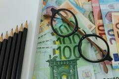 Foyer sélectif sur des verres sur d'euro billets de banque et crayons en tant que hausse Photographie stock