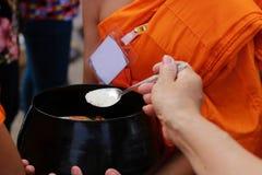 Foyer sélectif sur la cuillère des personnes tandis que la nourriture mise à l'aumône du ` un s de moine bouddhiste roulent en Vi images stock