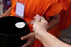 Foyer sélectif sur la cuillère Mains des personnes tandis que la nourriture mise à l'aumône du ` un s de moine bouddhiste roulent photographie stock