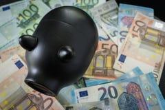 Foyer sélectif sur la tirelire noire sur la pile d'euro billets de banque As Images libres de droits