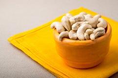 Foyer sélectif sur les noix de cajou crues dans une petite tasse orange Photographie stock