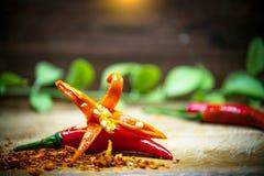 Foyer sélectif sur les poivrons de piment d'un rouge ardent frais avec le fond en bois et vert de feuilles Image stock