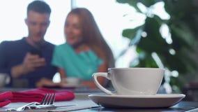 Foyer sélectif sur une tasse sur la table, couple caressant sur le fond banque de vidéos