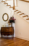 Foyer by Stairs. A nice foyer by interior stairs with table and flowers Royalty Free Stock Photos