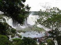 Foz robi Iguaçu, widok Iguazu spadki w odległości wśród gałąź las i przejście z wiele turystami, zdjęcia royalty free