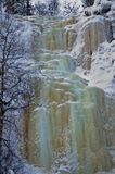 Fozen icy waterfalls colored in shades of green and brown in lapland. Winter and christmas in lapland is the time when waterfalls turn frozen royalty free stock images