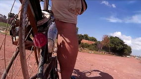 60 fps slow motion of a cyclist taking a series of turns on an unpaved rural road in Southeast Asia - rear mounted action cam reve. Als road and paths ahead, as stock footage