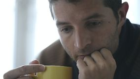 24 fps video shot hand held camera close up young man at home looking sad and drinking coffee stock footage