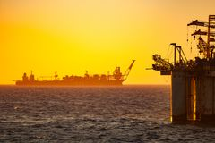 FPSO oil rig vessel silhouette and a drilling rig stock photo