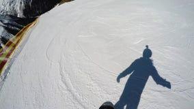 FPV在小山下的挡雪板倾斜 挡雪板的阴影 初学者水平 行动照相机在挡雪板的盔甲 影视素材