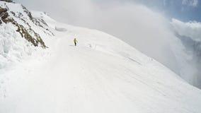 FPV在小山下的滑雪者倾斜 在滑雪者前面的Snowbarder倾斜 在山的晴朗的天气 Dombai 股票视频