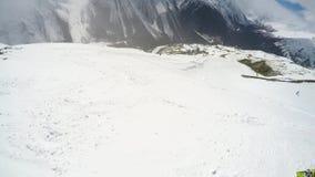 FPV pi? slier fare video dello snowboarder che pende gi? la collina sulla polvere della neve Giorno soleggiato in montagne nevose stock footage