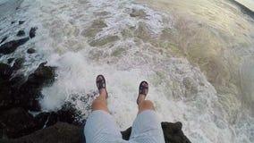 FPV: piernas contra la perspectiva de las ondas grandes que se estrellan contra las rocas en la cámara lenta estupenda almacen de metraje de vídeo