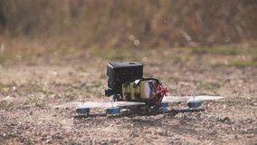 FPV racing drone takes off from a dirt surface raising dust and stones stock video footage