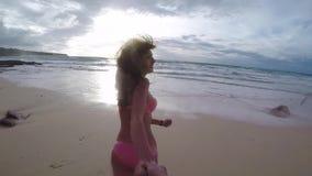 FPV: schönes Mädchen, das Hand und Läufe entlang dem Sand in den Ozean bei Sonnenuntergang in Bali, Zeitlupe hält stock footage