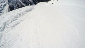 FPV Skier slopes down hill following shadow. Good weather for skiing. Action camera is on helmet. Skiers and stock video
