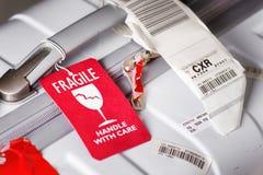 Frágil de la etiqueta del equipaje atado a la maleta blanca en el aeropuerto Imagen de archivo