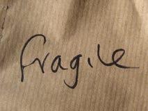 Frágil (manuscrito en la cartulina) Imagen de archivo libre de regalías