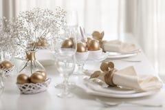 Fröhliche Ostern! Goldener Dekor und Gedeck der Ostern-Tabelle mit weißen Tellern der weißen Farbe lizenzfreie stockfotografie