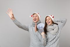 Fröhlicher Spaßpaar-Mädchenkerl in den grauen Strickjackenschals roten Santa Christmas-Hutes lokalisiert auf grauem Wandhintergru stockbild