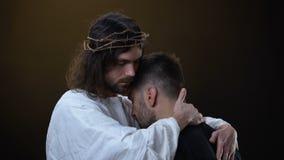 Frälsare i krona av biskopsstolar som kramar desperat manlig religiös fred, förlåtelse arkivfilmer