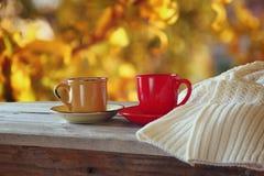 Främre bild av två kaffekoppar över trätabellen och den woolen tröjan framme av höstlig solnedgångbakgrund Royaltyfri Bild