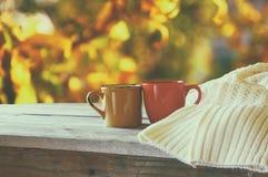 Främre bild av två kaffekoppar över trätabellen och den woolen tröjan framme av höstlig solnedgångbakgrund hjärta för gåvan för d Royaltyfri Foto