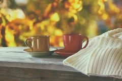 Främre bild av två kaffekoppar över trätabellen och den woolen tröjan framme av höstlig solnedgångbakgrund hjärta för gåvan för d Royaltyfri Fotografi