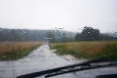 Främre bilfönsterexponeringsglas och torkare under hällregn Arkivfoton