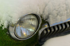 Främre billykta av en gammal bil i vinter bevuxen moss snowfall Royaltyfri Fotografi