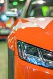 Främre billykta av en tävlings- röd bil för sportar, på den autobody autoexhibitionen arkivbilder