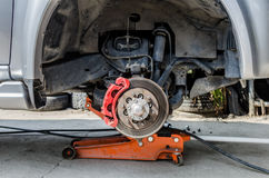 Främre diskettbroms på bilen i process av det nya däckutbytet Royaltyfri Bild