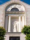 Främre fasad av församlingkyrkan med statyn av St John av Nepomuk, Woudrichem, Nederländerna royaltyfria bilder