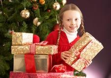 främre flicka för jul som rymmer den aktuella treen Royaltyfri Bild