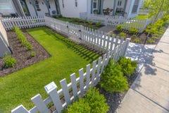 Främre gård med gräsmattor och buskar med det vita staketet royaltyfria bilder