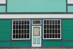 Främre ingång för litet lager som gör grön trähuset Fotografering för Bildbyråer
